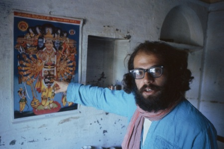 BENARES, INDIA - FEBRUARY 1963: Beat poet Allen Ginsberg points at art poster during February 1963 in his tenement apartment near the banks of the Ganges river in Benaras, India. Ginsberg explored Eastern philosophies with Peter Orlovsky and other founders of the Beat movement during his March '62 - May '63 stay. (Photo by Pete turner/Getty Images)